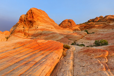 Yant Flat - red, orange, and white unusual striped rock formation in Southern Utah - glowing in sunrise.