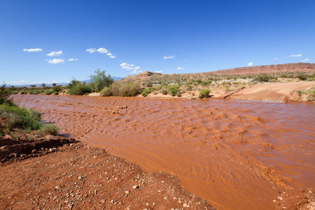 The dry wash is flooded with muddy water after rain storm in Southern Utah desert. The water blocked the dirt road and it was impassable.