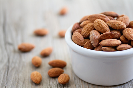 nuts: Bowl of almond nuts on rustic wooden table in natural light.