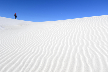 chihuahua desert: Photographer walking on white sand dunes, White Sands National Monument, New Mexico