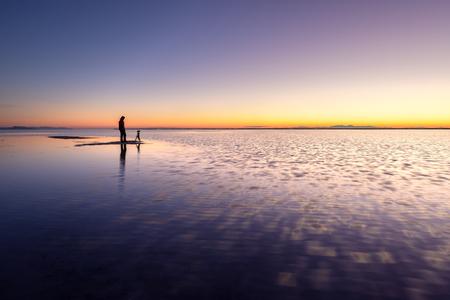 Photographer standing in the shallow water at dawn, Bonneville Salt Flats near Great Salt Lake, Utah