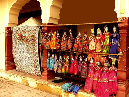 practiced: A number of wooden dummy dolls that are dressed up in bright and color attires.The puppets in Rajasthan are one of the popular sources of entertainment in the state. The art of puppetry is practiced by a community of agricultural laborers of Rajasthan.
