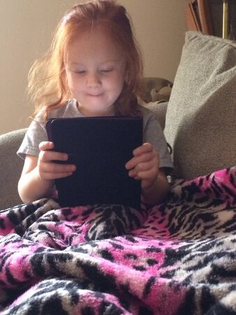 A four year old girl using a tablet Stock Photo