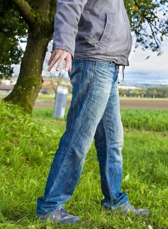 botar basura: Hombre tirando basura en la hierba