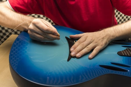 e guitar: String of a guitar is being renewed by a technician    Series with the same model available