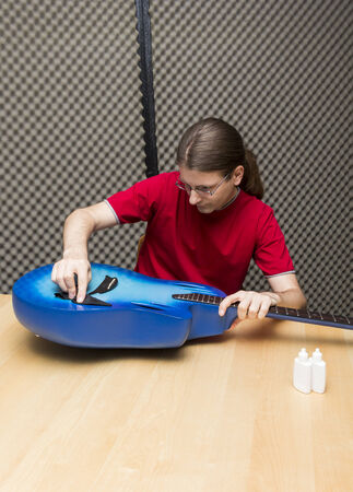 25 29 years: Guitarist cleaning his guitar with a cleaning towel    Series with the same model available  Stock Photo