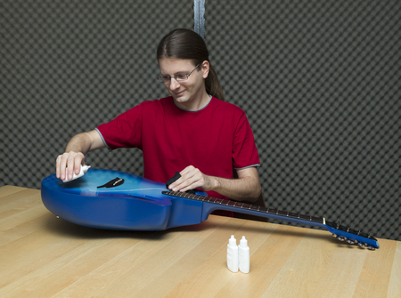 e guitar: Young guitarist cleaning and polishing his guitar    Series with the same model available  Stock Photo