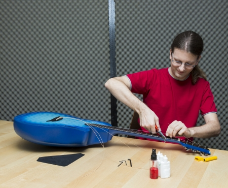 e guitar: Guitar technician cutting the old strings away    Series with the same model available