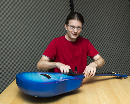 e guitar: Guitar technician cleaning the guitar    Series with the same model available  Stock Photo