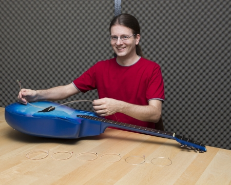 e guitar: Smiling guitarist changing the guitar strings   Series with the same model available  Stock Photo