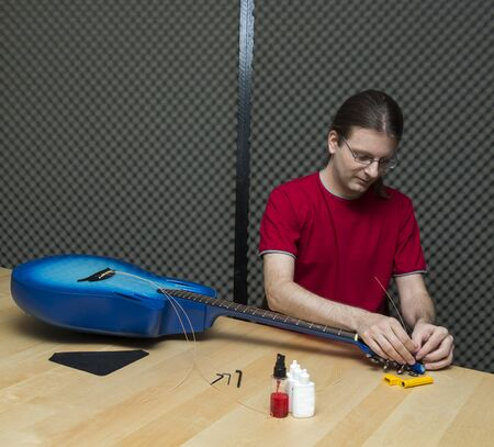 e guitar: Guitar technician replacing the strings of an electro-acoustic guitar   Series with the same model available