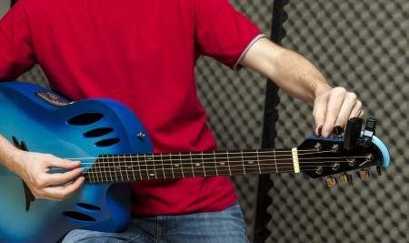 e guitar: Guitarist tuning his guitar   Series with the same model available  Stock Photo