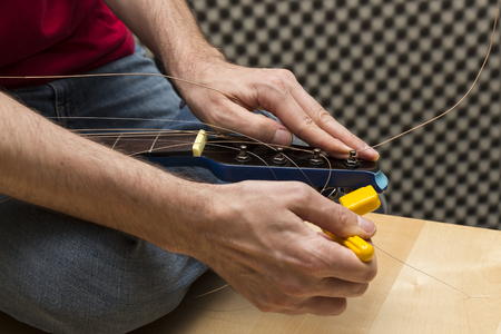 guitar tuner: Guitar technician is using the string winder