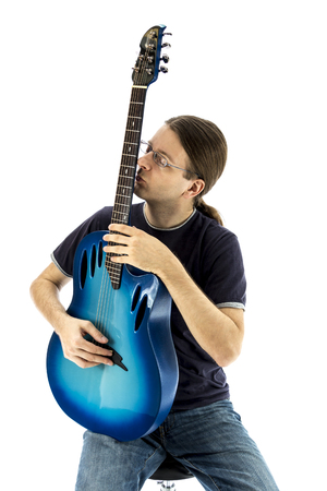 e guitar: Young guitarist sitting straight and kissing his electric guitar Stock Photo