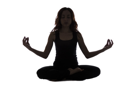 Young woman in silhouette view is in meditation pose. photo