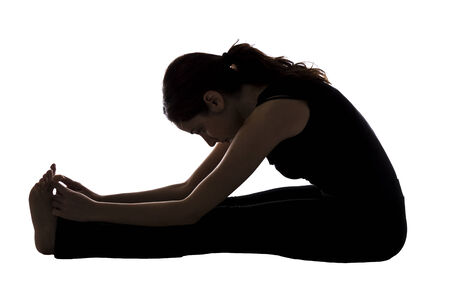 Woman is doing seated forward bend pose in yoga. photo