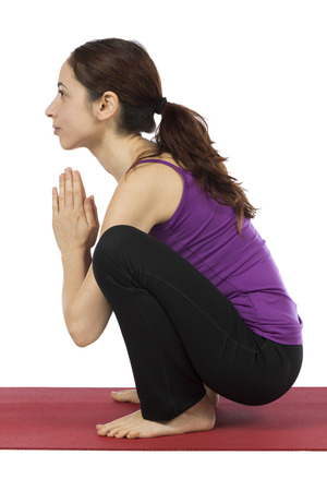 30 34 years: Young woman is doing Garland Pose in Yoga  Stock Photo