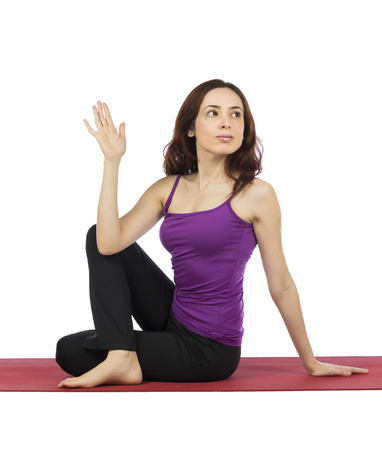 Young woman is doing Half Lord of the Fishes pose in yoga