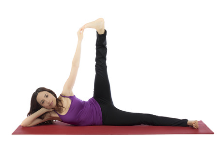 Young woman is doing pilates exercises with a leg raise