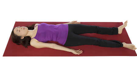 female pose: Woman is resting in Savasana during Yoga.