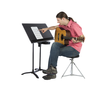 music notation: Guitar player is looking to the music notation sheets confused.
