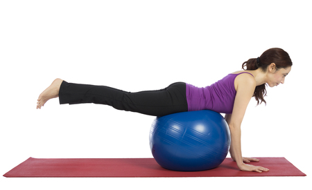 Woman is balancing on a pilates ball.