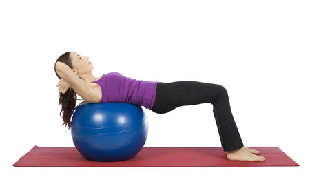 30 34 years: Young woman is doing crunch on a pilates ball