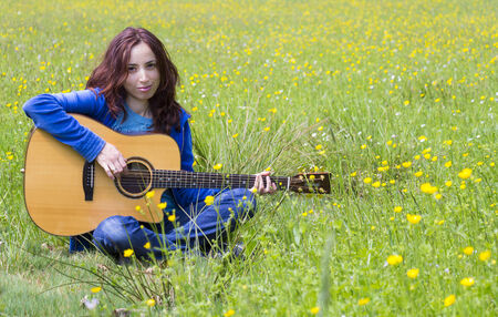 stitting: Young woman is stitting and playing acoustic guitar outdoors
