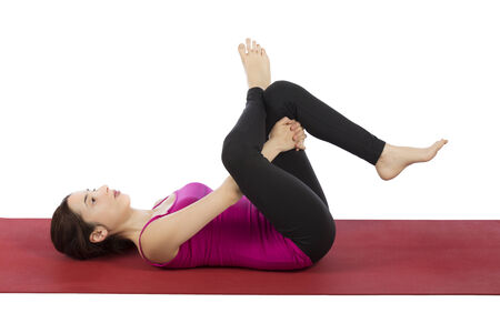 Woman is in eye of the needle pose in yoga.