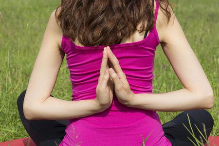 reverse: Woman is doing reverse namaste pose outdoors. Stock Photo