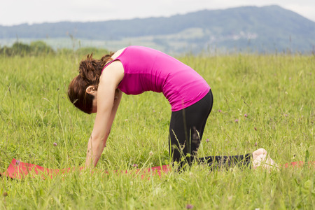 Young woman is doing cat pose in yoga outdoors in nature.