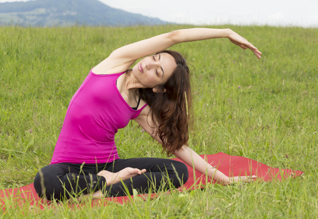 Young caucasian woman is stretching in nature outdoors.
