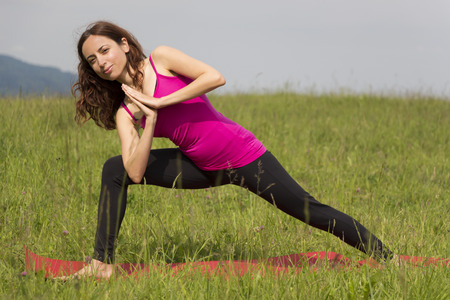 Woman is in high lunge pose during yoga outdoors.