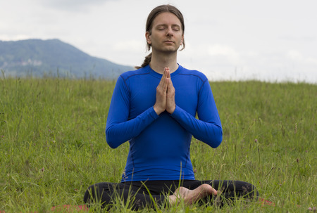 Man is meditating outdoors. photo