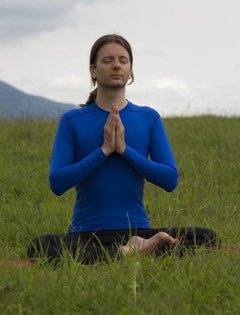 Man is in Namaste pose outdoors. photo