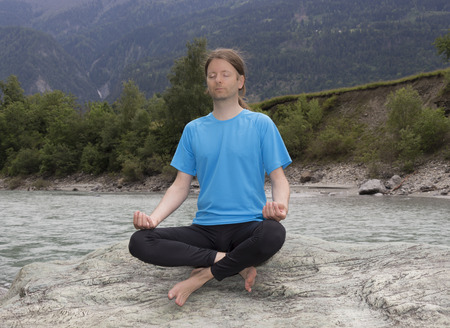 Young man is sitting on a rock and meditating in lotus pose. photo
