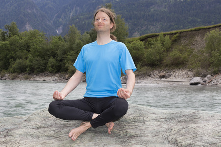 Young man is in meditation outdoors in nature. photo