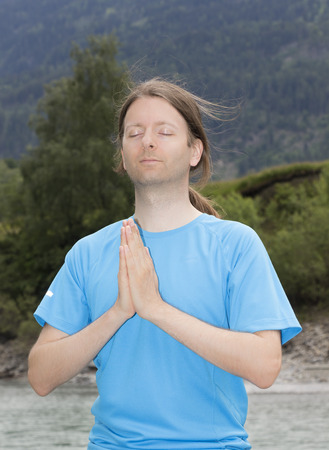 Young man is meditating outdoors by a river. photo