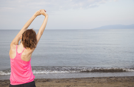 Woman is stretching her arms outdoors by a beach photo