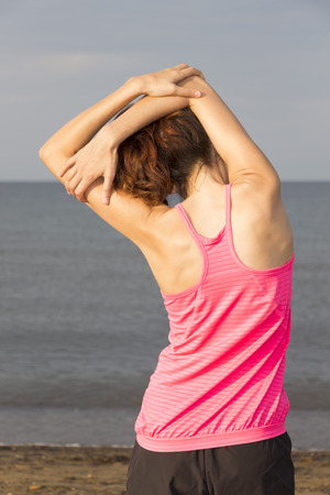 Woman is stretching on the beach. photo