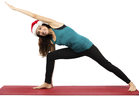 side angle pose: Yogi woman with santa hat stretching in extended side angle pose Stock Photo