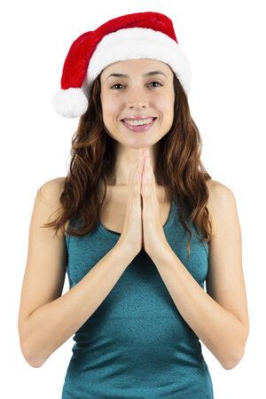 Yogi woman wearing a santa hat in namaste pose