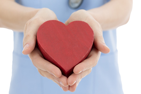 Doctor or nurse holding heart Stock Photo