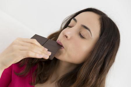 home confort: Caucasian woman enjoying her piece of dark chocolate Stock Photo