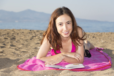 Woman relaxing and sunbathing on the beach photo