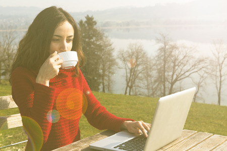 working: Woman working on laptop outdoors