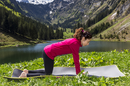 Woman in neutral pose during cat cow flow outdoors in nature Standard-Bild