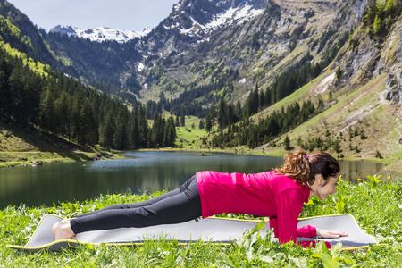 forearm: Woman doing forearm plank pose outdoors Stock Photo