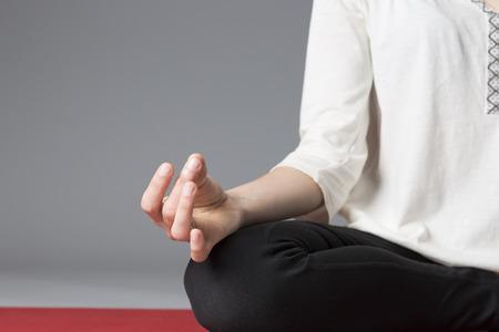 Female hand close up in lotus pose durig meditation. Grey background