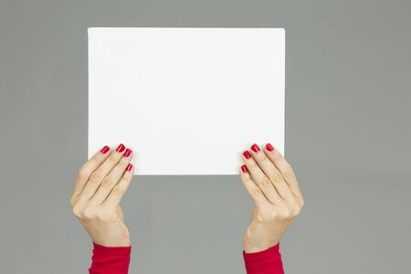 exhibiting: Woman hands holding a poster with copy space